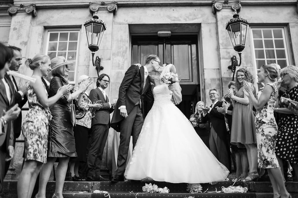 Kussend bruidspaar op de trappen van Huis de Voorst